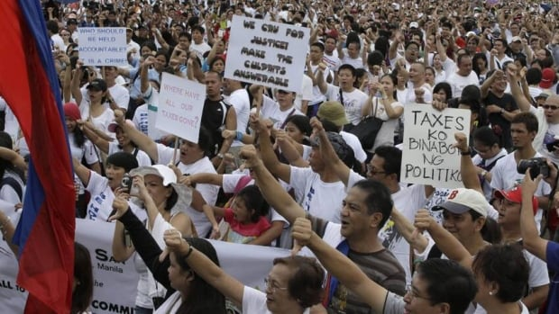 Tens of thousands of protesters flash thumbs-down signs during a rally at Rizal Park in Manila to call for the scrapping of a corruption-tainted government fund. The money allows legislators to allocate government cash for projects in their districts, but at least $226 million may have been embezzled.