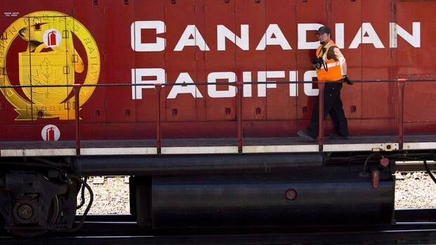 A Canadian Pacific Railway employee walks along the side of a locomotive in a marshalling yard in Calgary in 2012. CP is cutting a number of positions, including four safety inspectors across the border in Cranbrook, B.C.