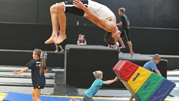 Jacob Terrell flips as others play at the Get Air Hang Time indoor trampoline park in Orem, Utah, where customers get a a chance to bounce, flip and jump on wall-to-wall trampolines.