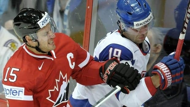 Canada's Ryan Getzlaf, left, checks Slovakia's Tomas Starosta on Friday in the world hockey championship opener for both teams.