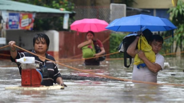 Residents wade through a flooded street in Manila. Officials reported at least seven people dead, 11 injured and four missing.