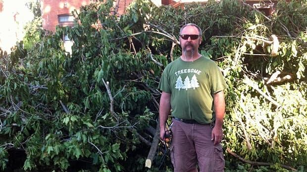 Esther Lockhart's husband Mike, and the tree that came down by their home. They've been without power since Friday evening.