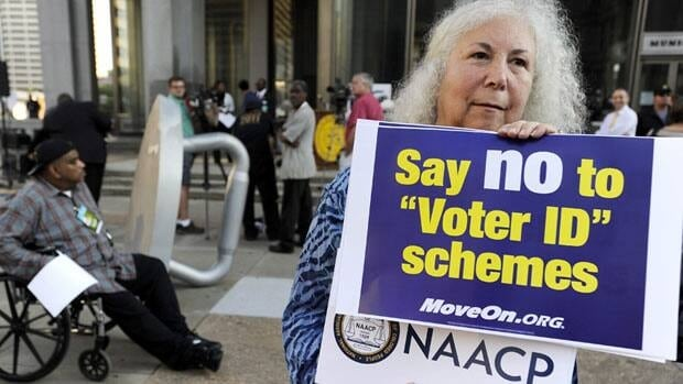 Gloria Gilman holds a sign during a NAACP voter ID rally last month to demonstrate the opposition of Pennsylvania's voter identification law. Republicans are being criticized by some civil rights groups for creating voter ID laws that would affect and suppress mostly poor or minority voters.