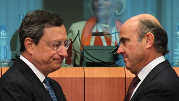 Spanish Finance Minister Luis de Guindos Jurado, right, talks with President of the European Central Bank Mario Draghi during the Eurogroup ministerial meeting at the European Council building in Brussels, Monday. European finance ministers are trying to secure Spain's teetering economy.