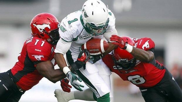 Roughriders' Kory Sheets, middle, tries to run the ball past Stampeders' Malik Jackson, left, and Fred Bennett in the first quarter.