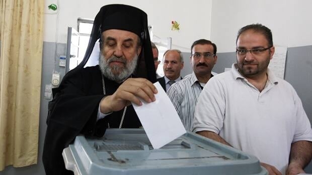 A Syrian Christian cleric casts his vote for the parliamentary elections at a polling station in Damascus on Monday.