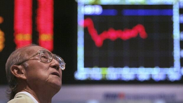 An investor looks at the share index at a private stock market gallery in Kuala Lumpur, Malaysia.