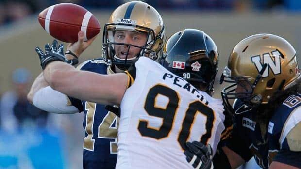 Winnipeg Blue Bombers quarterback Joey Elliott throws despite pressure from Hamilton's Greg Peach during the first half.