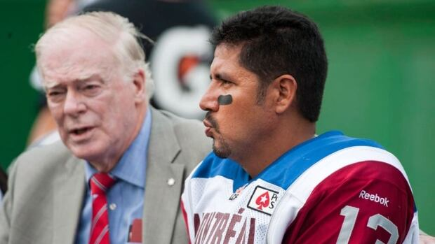Montreal Alouettes medical staff member talks to quarterback Anthony Calvillo after during the game against the Saskatchewan Roughriders in Regina on Saturday, Aug. 17, 2013.