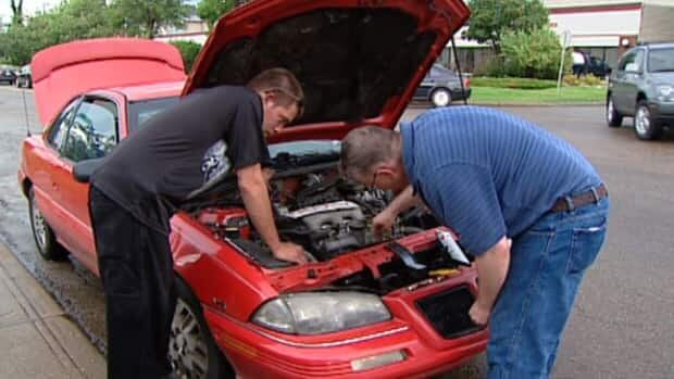 Richard McPhee (left) looks at his car engine which was flooded by rising water during Tuesday's storm.