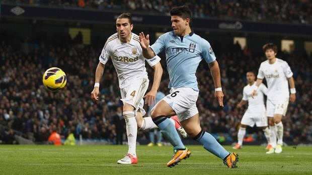 Manchester City's Sergio Aguero, centre-right, fights for the ball against Swansea's Chico during their match at The Etihad Stadium in Manchester, England on Saturday.