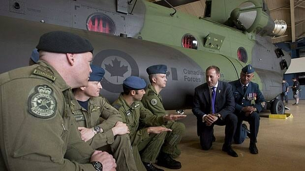 Former Defence Minister Peter MacKay speaks with the crew of a new Chinook helicopter during an event on June 27 in Ottawa. He was moved to the justice portfolio in Monday's cabinet shuffle and Prime Minister Stephen Harper also eliminated the associate minister of defence position.