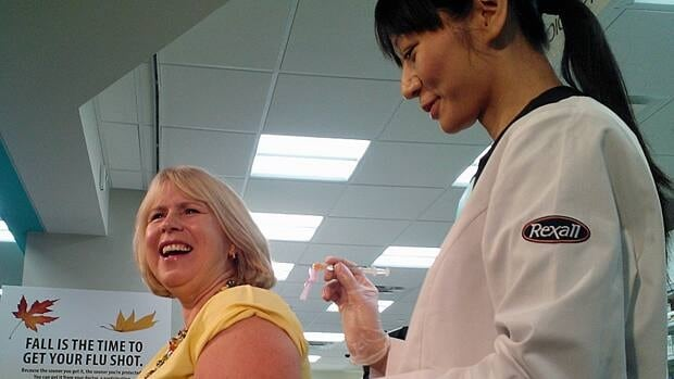 Ontario Health Minister Deb Matthews receives a flu shot at a Toronto pharmacy. Phamacists in British Columbia, Alberta and New Brunswick can also give the vaccine.