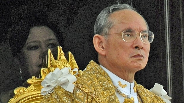 Thailand's King Bhumibol Adulyadej looks to hundreds of thousands of Thais gathered as Queen Sirikit waits in the shadows on June 9, 2006, at Bangkok's Royal Plaza during celebrations marking his 60th anniversary on the throne.