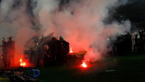 Riot police take cover as Fenerbahce fans launch flares and seats at the end of the Turkish Super League championship match in Istanbul, Turkey on Saturday. Murad Sezer/Reuters
