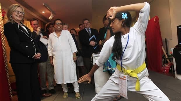 U.S. Secretary of State Clinton watches a girl do karate during an anti-human trafficking event in Kolkata.