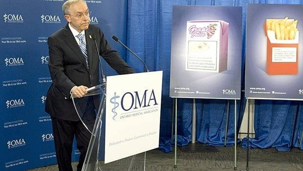 Dr. Doug Weir, president of the Ontario Medical Association, stands in front of depictions of health warnings on fast foods.