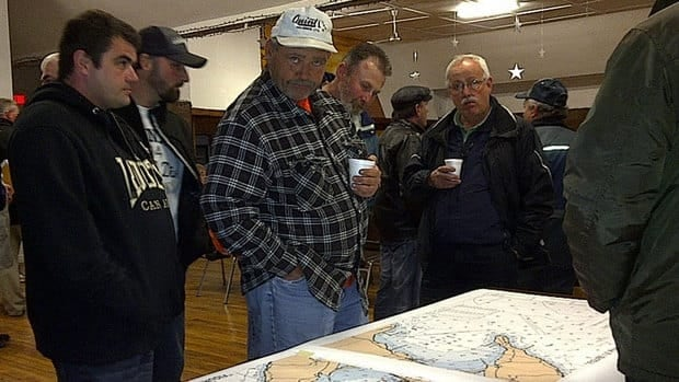 Fishermen look over a map at a meeting Wednesday.