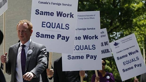 Tim Edwards, left, president of the Professional Association of Foreign Service Officers, protests in front of the Canadian embassy in Washington in May. He said Monday the strike is causing a severe and mounting economic impact.