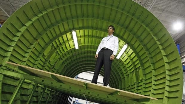 Patrick Tessier, a Bombardier engineer, stands within a CSeries aircraft fuselage test barrel at the firm's Montreal plant. Bombardier said it now expects the plane to have its first CSeries flight before the end of next June.