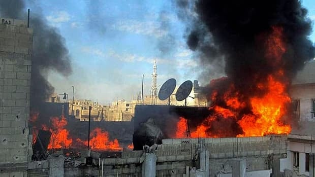 Flames rise from a house battered by Syrian government shelling at Baba Amr neighborhood in Homs, Syria.