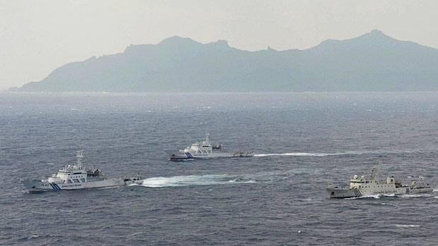 Japan Coast Guard vessels sail along with a Chinese surveillance ship, right, near disputed islands called Senkaku in Japan and Diaoyu in China, seen in the background, in the East China Sea, on Monday. China said Monday it plans to deploy unmanned drones in an effort to beef up surveillance around the disputed territory by 2015.