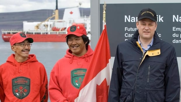 Prime Minister Stephen Harper poses for a photograph with Canadian Rangers during the August 2007 announcement of plans for a naval refuelling facility at the site of the dock for the defunct Nanisivik mine near Arctic Bay, Nunavut. The cost of the development ballooned from $100 million to $258 million before the plans were scaled back.