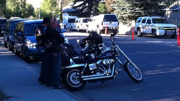 Two men wearing Hells Angels patches watch as a clubhouse is raided in Kelowna, B.C.