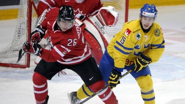 Canada's Tyler Wotherspoon, left, and Sweden's Elias Lindholm compete in an exhibition game Saturday at the world junior hockey championship.