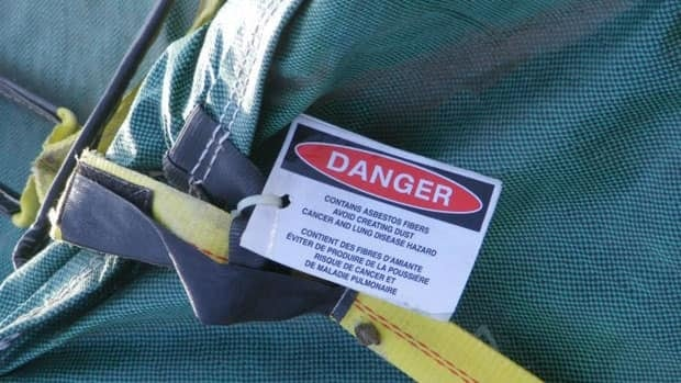 The bags are tagged with a warning that states the material is a 'Cancer and Lung Disease Hazard.'