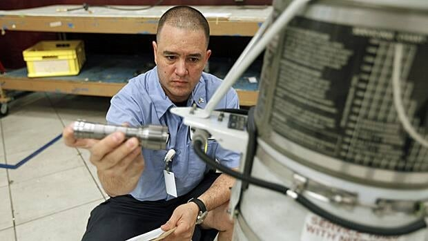 A landing gear inspector is shown working in Medley, Florida. The U.S. economy added 243,000 jobs last month, its best showing since April.