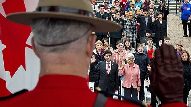 An RCMP officer raises his hand as a group of 60 people take the oath of citizenship in Vancouver. The federal government is proposing changes that will require some people to wait longer before they are eligible to become citizens.