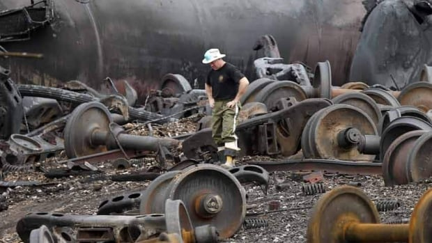 A police officer walks amongst axle gear in Lac-Mégantic after the train derailment that levelled the town's centre and left 47 dead.
