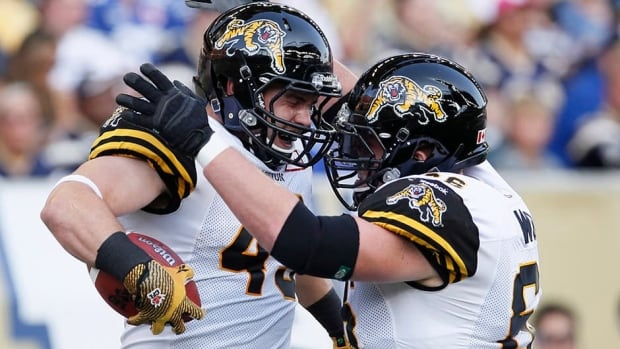 Tiger-Cats' John Delahunt, left, and Greg Wojt celebrate Delahunt's touchdown against the Winnipeg Blue Bombers during the first half of their CFL game in Winnipeg on Friday. Hamilton went on to win the game 37-18.