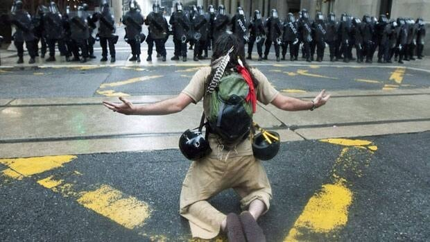 A protester reacts to the riot police while marching along the streets of downtown Toronto during the G20 summit on June 26, 2010.