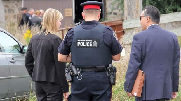 A pair of Toronto police detectives speak with a Waterloo Regional Police officer as investigators search the Dellen Millard farm in North Dumfries Township.