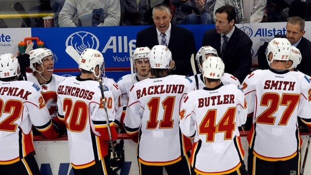Calgary Flames head coach Bob Hartley, centre, seen here talking to his players, has chosen a successor for former team captain Jarome Iginla. Many of the Flames players believe it will be defenceman Mark Giordano.