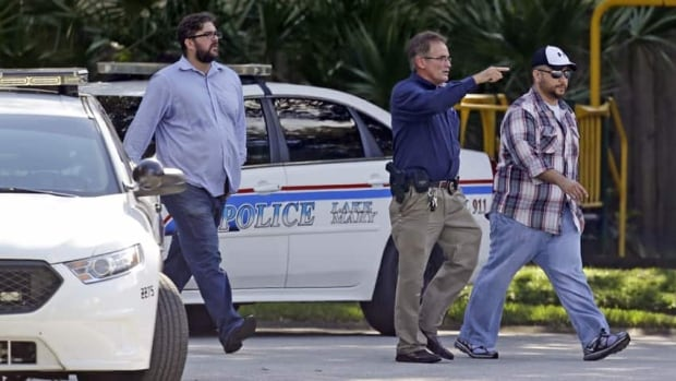 George Zimmerman, far right, is escorted by a Lake Mary police officer, centre, and Shawn Vincent, an assistant to his attorney on Monday. Zimmerman was recently found not guilty for the 2012 shooting death of Trayvon Martin.
