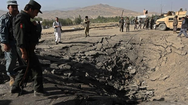 Afghan policemen stand near a crater at the scene of a suicide attack in Maidan Shar, capital of Wardak province, on Sunday. Taliban militants detonated a car bomb outside an Afghan intelligence office near the capital. At least four soldiers guarding the compound were killed and six insurgents died in the assault, officials said.