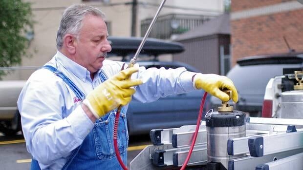 Doug Rondeau pulls an insecticide sprayer from the back of his truck.