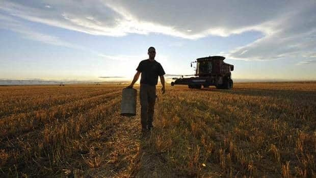 A worker carries an air filter during wheat harvest on the Stephen and Brian Vandervalk farm near Fort MacLeod, Alta. Alberta, Saskatchewan and Ontario saw the biggest jumps in price per acre for farmland this year.