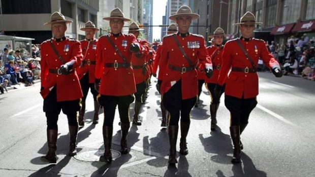 A group of RCMP offices march in the Calgary Stampede parade last summer. RCMP members who want to form an independent union took their arguments to the Supreme Court of Canada Tuesday.