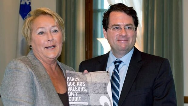 Quebec Premier Pauline Marois receives the tables Charter of Quebec values from Minister Responsible for Democratic Institutions and Active Citizenship, Bernard Drainville.