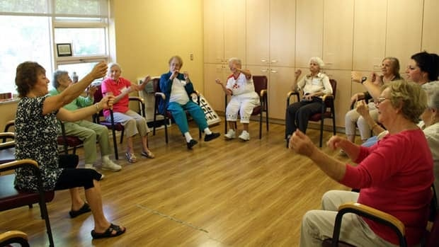 A staff member at Alzheimer Society of Sudbury-Manitoulin leads seniors in a class called Ageless Grace. They pretend to play musical instruments to the sound of pop music.