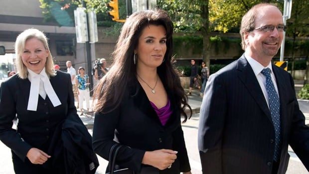 Vancouver Canucks co-owner Francesco Aquilin's wife Taliah, centre, leaves the B.C. Supreme court in downtown Vancouver on Monday as the couple finalized a divorce settlement.