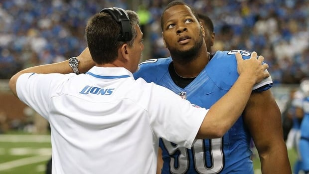 "Detroit Lions head coach Jim Schwartz talks with Ndamukong Suh, who said Wednesday he plans to play ""hard, blue-collar football"" despite his fine."