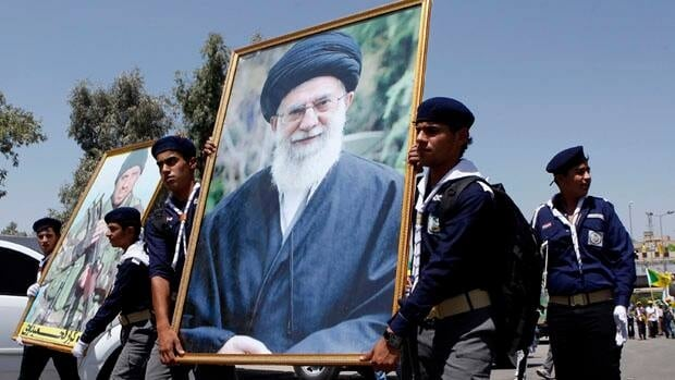 Iraqi Hezbollah members parade in Baghdad with a portrait of Iran's supreme leader Ayatollah Ali Khamenei last month. Iranian-backed Shiite militias are threatening to retaliate against American interests inside Iraq if the United States goes ahead with strikes against Syrian President Bashar al- Assad's regime, a close ally of Tehran.