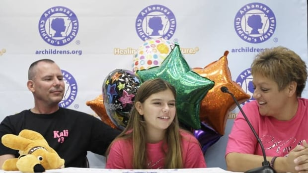 Parents Joseph Hardig, left, and Traci Hardig, right, watch as their daughter Kali Hardig, 12, speaks to reporters at Arkansas Children's Hospital. Kali survived a rare and often fatal infection caused by a brain-eating amoeba.