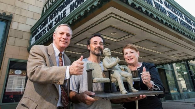 Sculpter Rick Harney, centre, holds a scale model of a sculpture of Roger Ebert in front of the Virginia Theatre in Champaign, Ill. Harney is flanked by Scott and Donna Anderson who announced a campaign to raise money for the commemorative sculpture of Ebert on Tuesday.