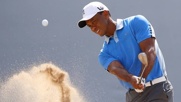 Tiger Woods hits out of the bunker on the 18th hole during the Pro-Am round of the BMW Championship golf tournament at the Conway Farms Golf Club in Lake Forest, Illinois on Wednesday.